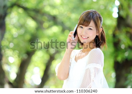 Portrait of beautiful young woman,speaking on mobile phone at summer green park. - stock photo