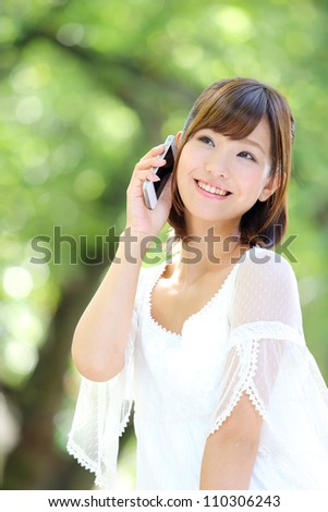 Portrait of beautiful young woman,speaking on mobile phone at summer green park.