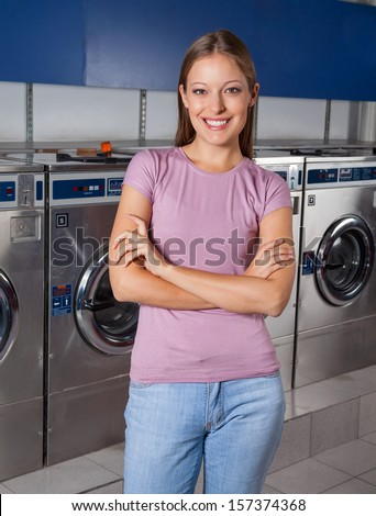 Portrait of beautiful young woman standing arms crossed with washing machines in background - stock photo