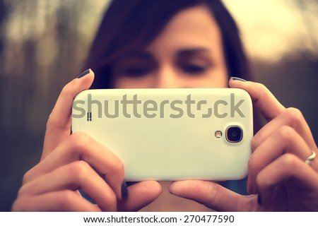 Portrait of beautiful young woman take a photo with mobile phone - stock photo
