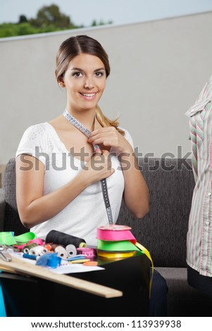 Portrait of beautiful young woman taking measurement of neck with dressmaking accessories on table