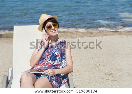 Portrait of beautiful young woman talking on the phone on the beach