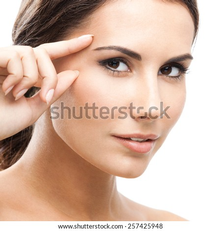 Portrait of beautiful young woman touching skin or applying cream, isolated against white background - stock photo
