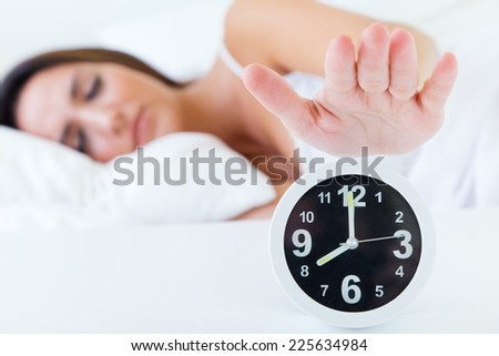 Portrait of beautiful young woman turning off the alarm clock. - stock photo