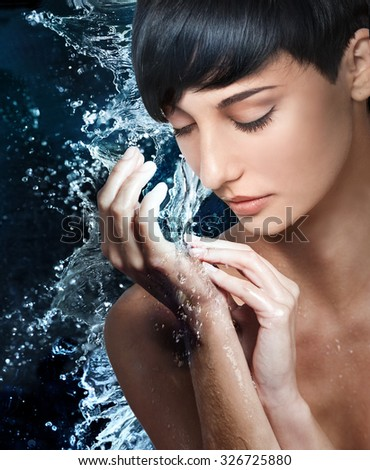 Portrait of beautiful young woman under stream of water falling on her hands  - stock photo