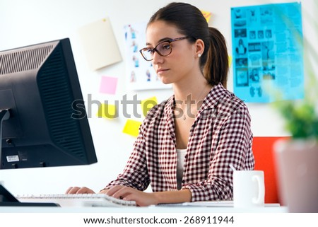 Portrait of beautiful young woman using her laptop in the office. - stock photo