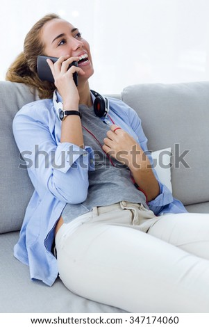 Portrait of beautiful young woman using her mobile phone at home. - stock photo