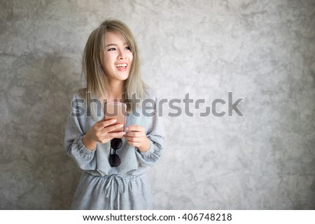 Portrait of beautiful young woman using her smartphone and looking to a side. - stock photo