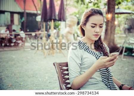Portrait of beautiful young woman using on smartphone in cafe background  - stock photo