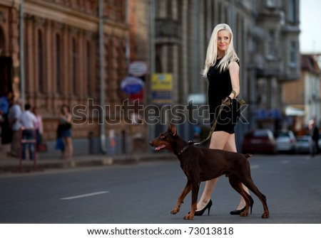 Portrait of beautiful young woman walking a dog - stock photo