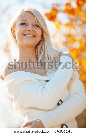 Portrait of beautiful young woman walking outdoors in autumn - stock photo