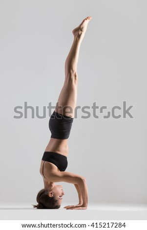 Portrait of beautiful young woman wearing black sportswear working out in studio. Fit sporty girl doing advanced yoga, pilates, fitness. Supported headstand, salamba sirsasana. Full length. Side view - stock photo