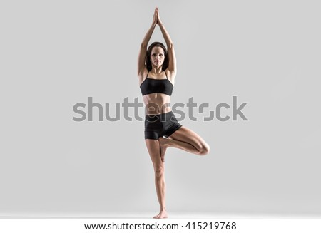 Portrait of beautiful young woman wearing black sportswear working out in studio. Fit sporty girl doing yoga, pilates, fitness exercise. Vrksasana Posture, Tree Pose. Full length. Horizontal image - stock photo