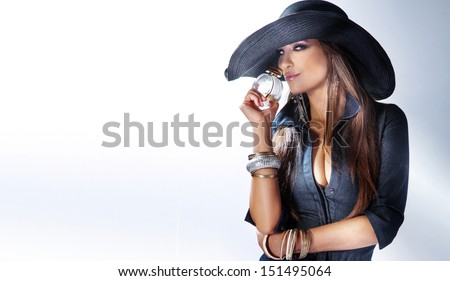 Portrait of beautiful young woman wearing hat, smelling perfume. - stock photo
