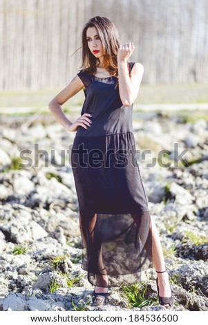 Portrait of beautiful young woman wearing long dress in a forest - stock photo