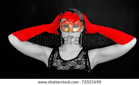 Portrait of beautiful young woman wearing red Italian glows and  mask. Shooting for black carnival.