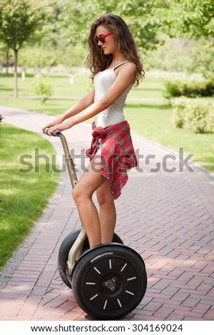 Portrait of beautiful young woman wearing red sunglasses. Girl using segway. Green alley as background - stock photo
