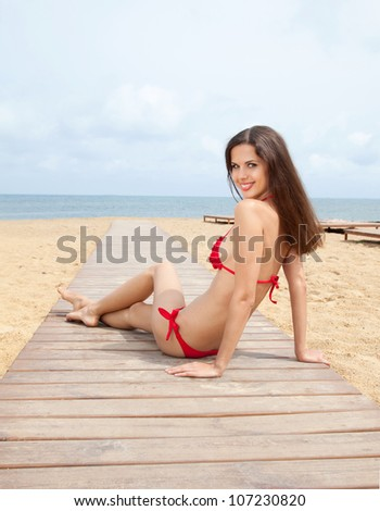 Portrait of beautiful young woman wearing red swimming suit  resting at the beach in summer - stock photo