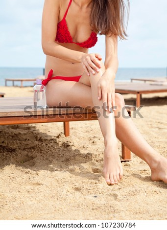 Portrait of beautiful young woman wearing red swimming suit  tanning at the beach in summer - stock photo