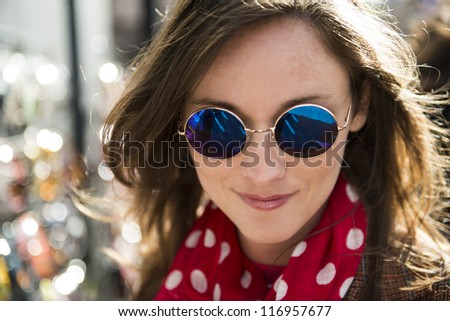 Portrait of beautiful young woman wearing round tinted sun glasses