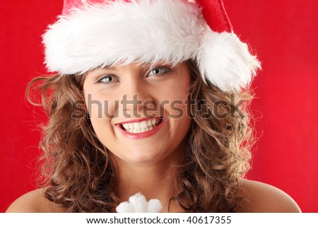 Portrait of beautiful young woman wearing santa claus hat on red background