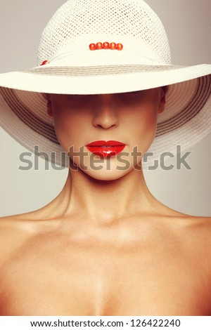 Portrait of beautiful young woman wearing straw hat - stock photo