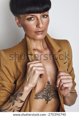 Portrait of beautiful young woman wearing suit. With black mushroom hair cut, tattoos on her body and sexy looking at camera. Developed from RAW. Retouched with special care and attention.  - stock photo