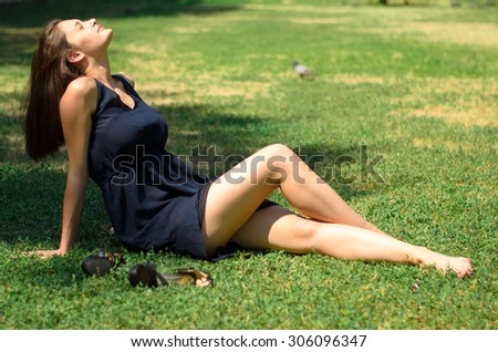 Portrait of beautiful young woman which sits on green grass