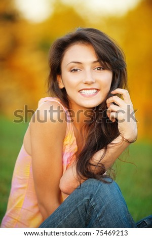 Portrait of beautiful young woman which sits on green grass on natural background - stock photo