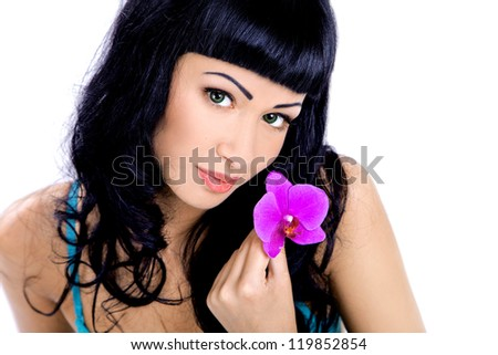 Portrait of beautiful young woman with an orchid flower - stock photo