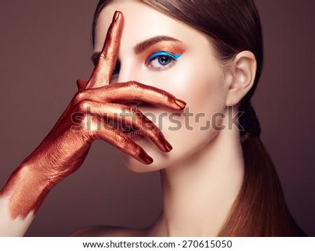 Portrait of beautiful young woman with art make-up. Bronze hand. Beauty fashion - stock photo