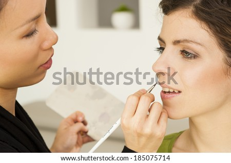 Portrait of beautiful young woman with asian esthetician making makeup - close up - stock photo