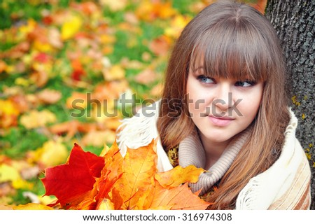 Portrait of beautiful young woman with autumn leaves - stock photo
