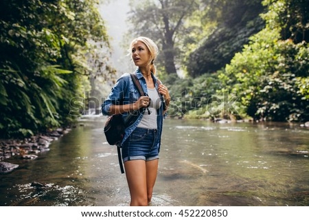 Portrait of beautiful young woman with backpack standing by the creek. Female hiker hiking by the mountain stream. - stock photo
