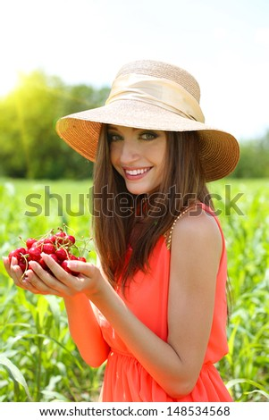Portrait of beautiful young woman with berries in the field - stock photo