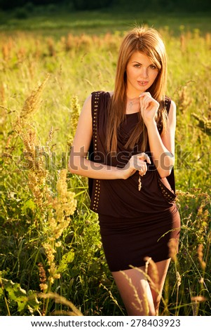 Portrait of beautiful young woman with blade of grass