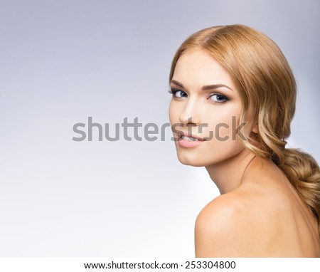 Portrait of beautiful young woman, with blank copyspace area for text or slogan, against grey background - stock photo
