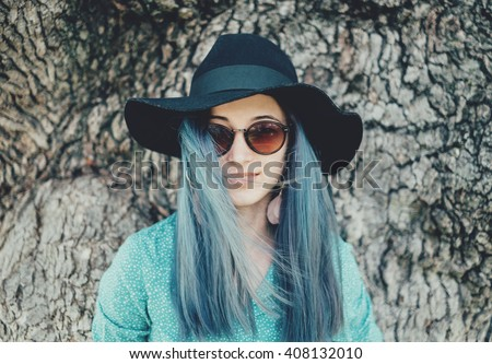 Portrait of beautiful young woman with blue hair wearing in hat and sunglasses on background of tree trunk, woman looking at camera