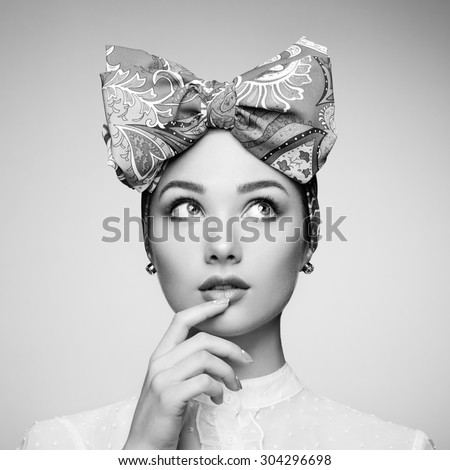 Portrait of beautiful young woman with bow. Brunette girl. Beauty fashion. Cosmetic make-up. Black and white - stock photo