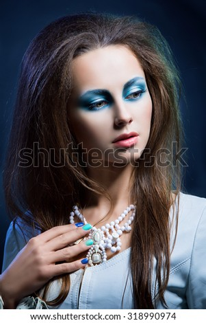 Portrait of beautiful young woman with bright blue makeup dressed in winter style over dark background