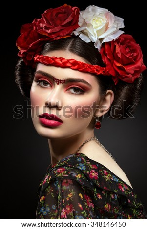 Portrait of beautiful young woman with bright red make up and roses on head. Over black background - stock photo