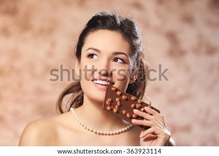 Portrait of beautiful young woman with chocolate, close up - stock photo