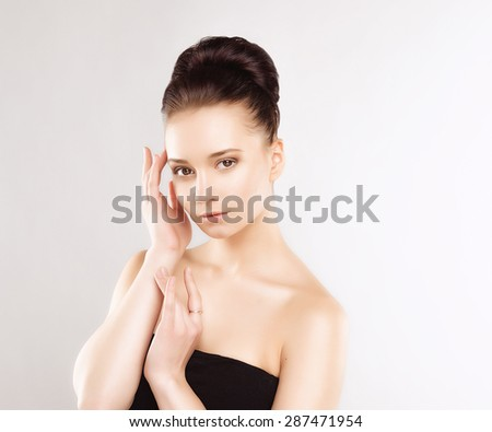 Portrait of Beautiful Young Woman with Clean Fresh Skin and Nude MakeUp. Isolated on Grey Background. Close up - stock photo