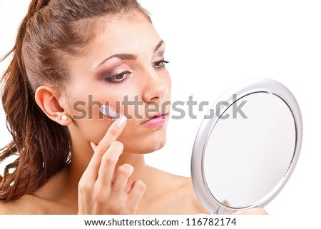 Portrait of beautiful young woman with cream on her face - stock photo