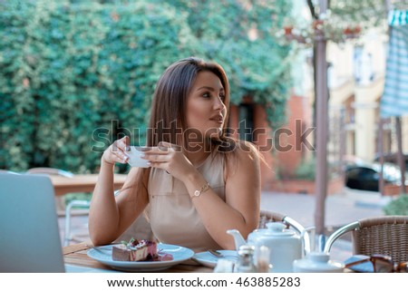 portrait of beautiful young woman with cup of tea in her hands outdoors looking away