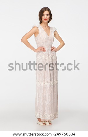 Portrait of beautiful young woman with curly hair wearing white evening dress, isolated on white background