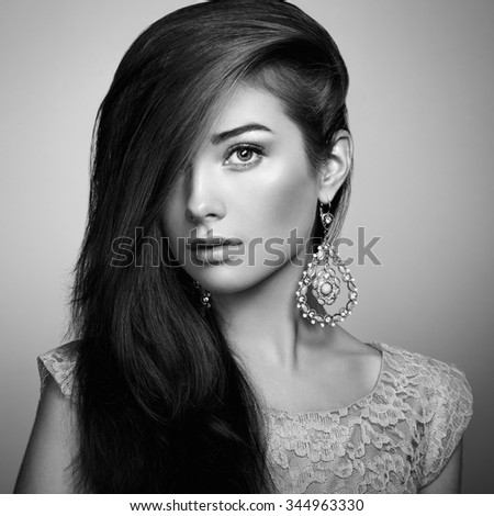 Portrait of beautiful young woman with earring. Jewelry and accessories. Perfect makeup. Fashion photo - stock photo