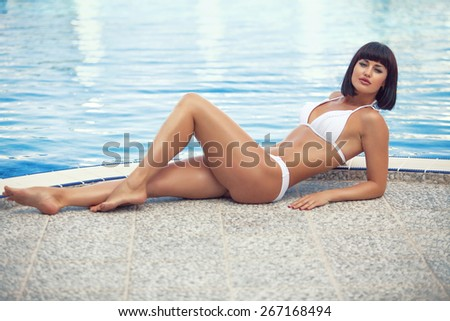 Portrait of beautiful young woman with fine figure resting at beach in summer