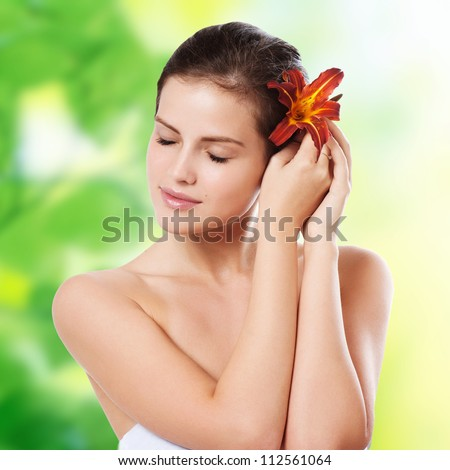Portrait of beautiful young woman with flower in her hair - stock photo