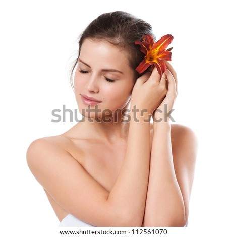 Portrait of beautiful young woman with flower in her hair